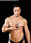 Funny picture of a male body builder from the waist up holding a tiny little trophy. The man has huge muscles, and a great six pack. The dude is rippling with muscles. Wearing a blue thong.